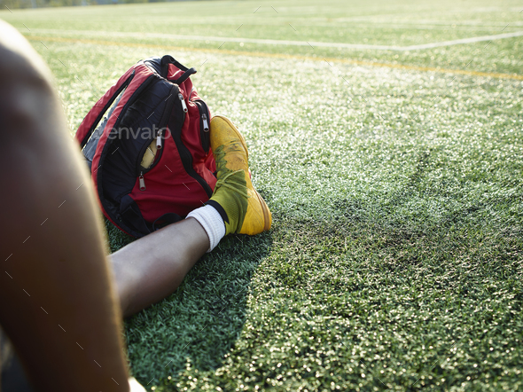 Boy wearing yellow sport shoe sitting on a lawn, a backpack at this feet. - Stock Photo - Images