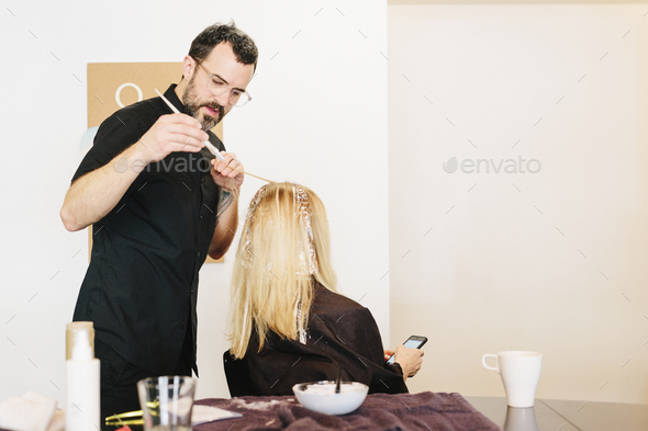 A hair colourist working with foils to give a client with long blonde hair highlights and lowlights - Stock Photo - Images