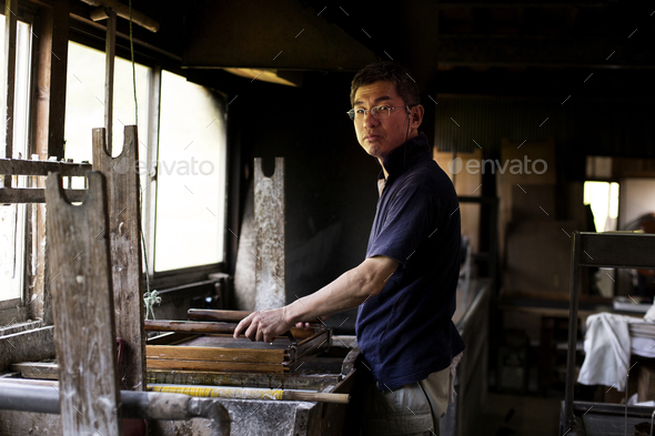 Japanese man in a workshop, holding a wooden frame with pressed pulp, making traditional Washi - Stock Photo - Images