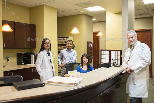 Caucasian male and east Indian woman ophthalmologists in their office with their staff employees. - Stock Photo - Images