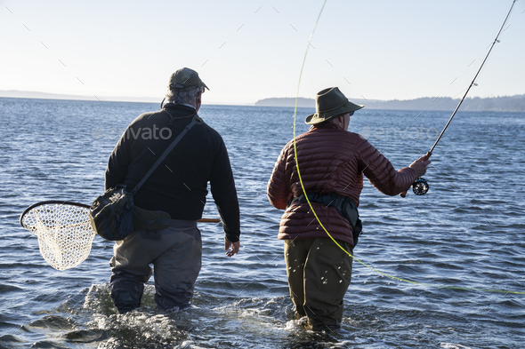 A guide advises his client while fly fishing in salt water for searun coastal cutthroat trout and - Stock Photo - Images