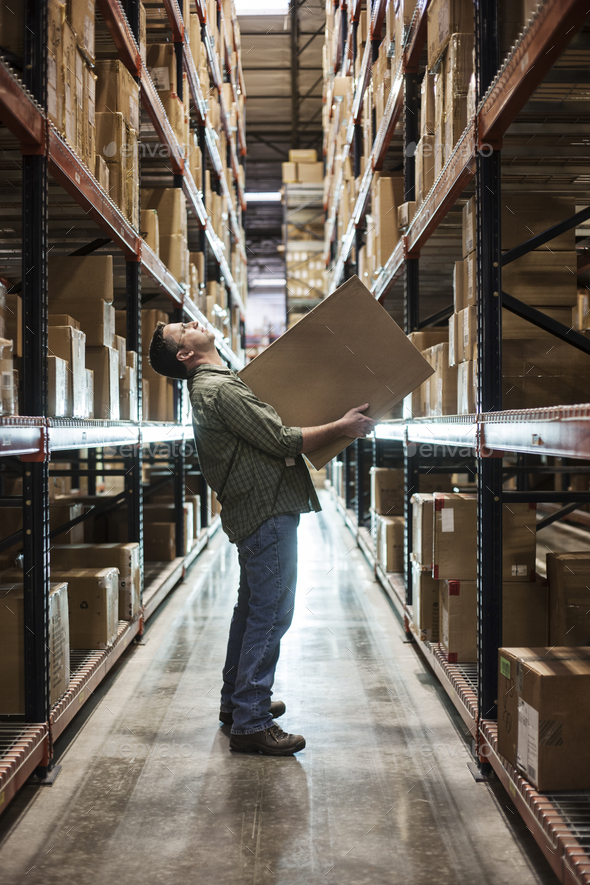Caucasian male warehouse worker standing in an aisle, holding a box and checking inventory on stacks - Stock Photo - Images