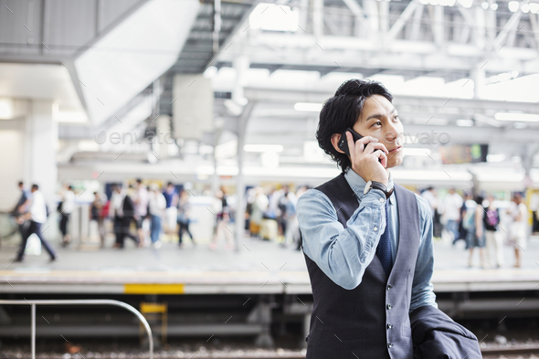 Businessman wearing suit standing on train station platform, holding mobile phone. - Stock Photo - Images