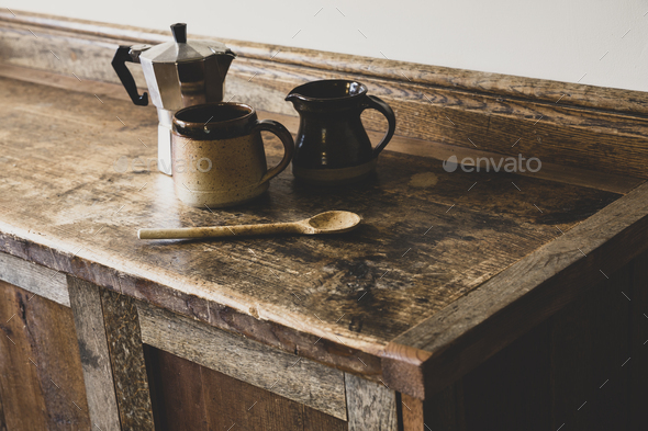 High angle close up of Espresso maker, earthenware mug and jug and wooden spoon on vintage wooden - Stock Photo - Images