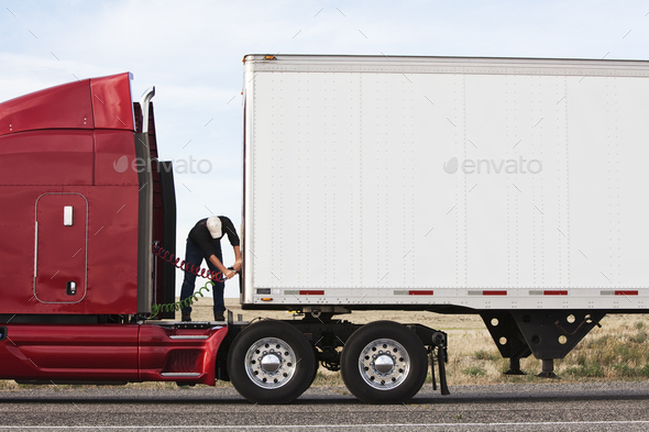 View of a driver connectiing the power cables to trailer of a  commercial truck. - Stock Photo - Images