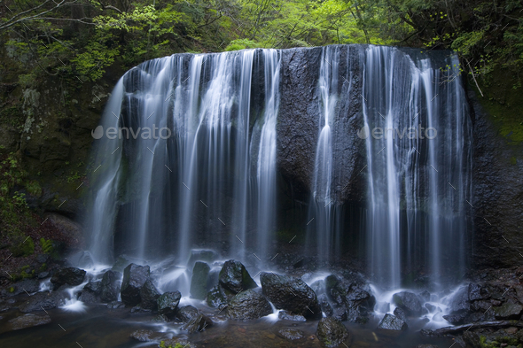 Long exposure of rocky waterfall in forest. - Stock Photo - Images