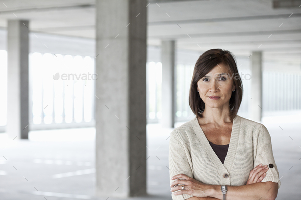 Caucasian businesswoman in a large empty raw office space. - Stock Photo - Images