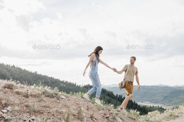 A couple in the mountains walking hand in hand. - Stock Photo - Images