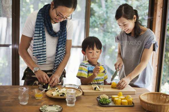 Man, woman and boy standing at a table, preparing corn on the cob, smiling. - Stock Photo - Images