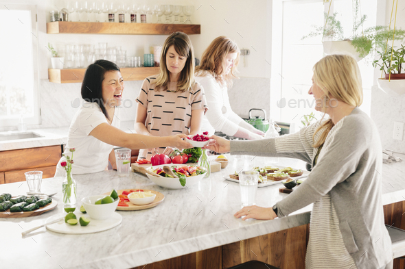 Four women in a kitchen preparing lunch. - Stock Photo - Images