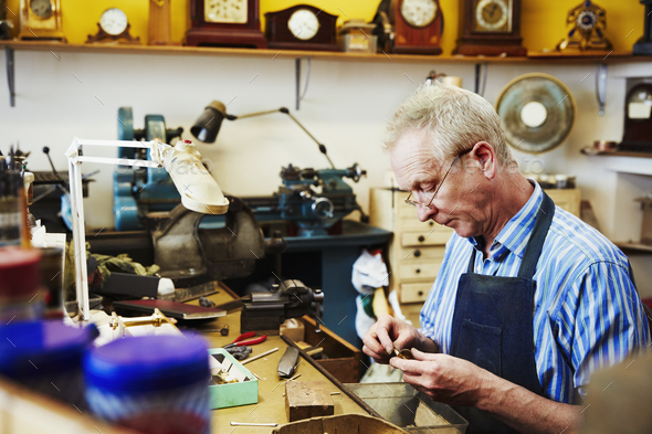 A clock maker working repairing the small parts of a clock. - Stock Photo - Images