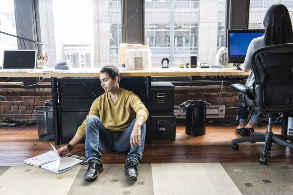 Hispanic man sitting on floor next to his work station in a creative office.