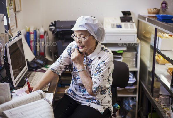 A mature woman at a desk in the office of a noodle production factory on the telephone. - Stock Photo - Images