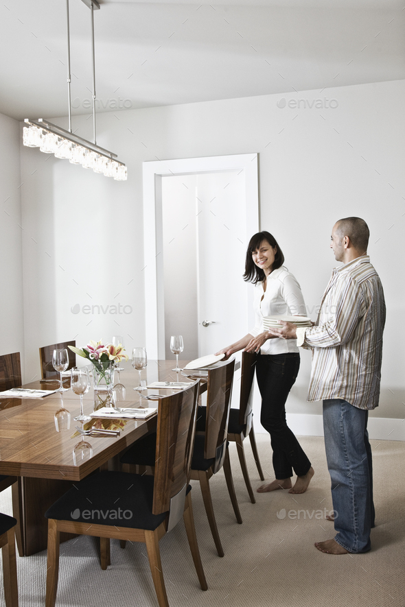 Hispanic man and woman doing place settings at their dinning room table in a new home. - Stock Photo - Images