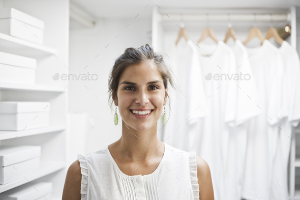 Portrait of HIspanic woman in a closet full of white clothes. - Stock Photo - Images