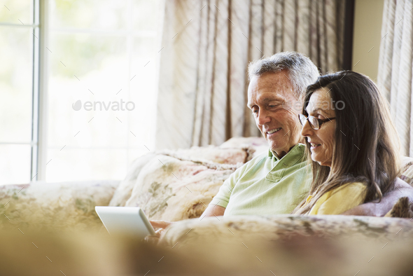 Smiling senior couple sitting on a sofa, using a laptop computer. - Stock Photo - Images