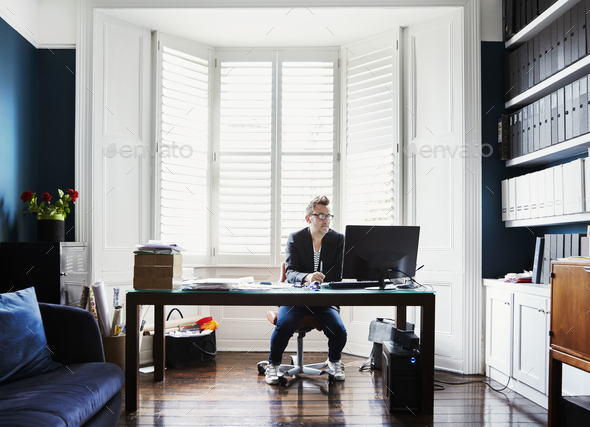A man in suit and trainers with glasses, sitting at a desk in a bay window. A light airy office with - Stock Photo - Images
