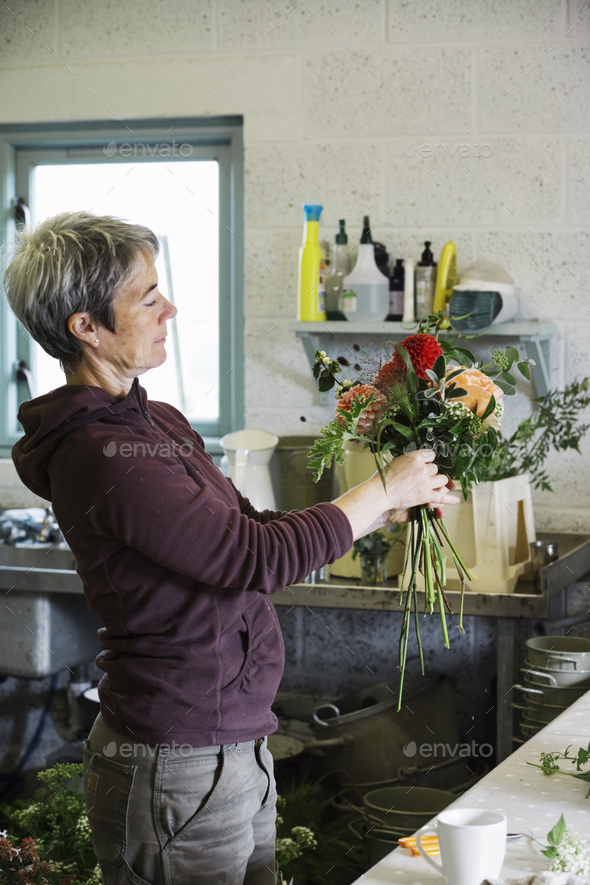 Organic flower arrangements. A woman creating a hand tied bouquet. - Stock Photo - Images