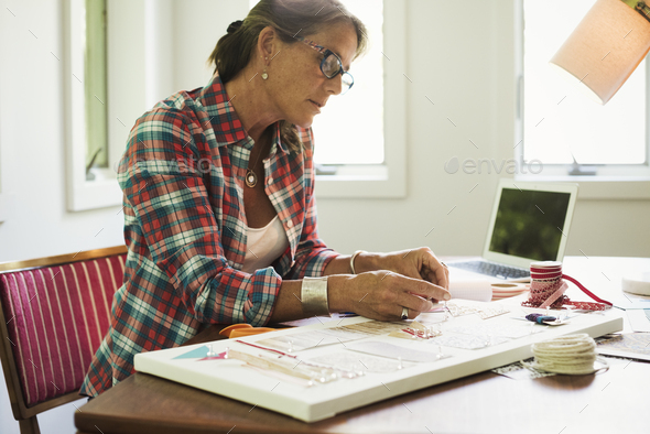 A woman creating a collage picture with material and paper. - Stock Photo - Images