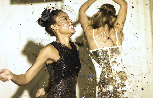 Two young women dancing with confetti falling. - Stock Photo - Images