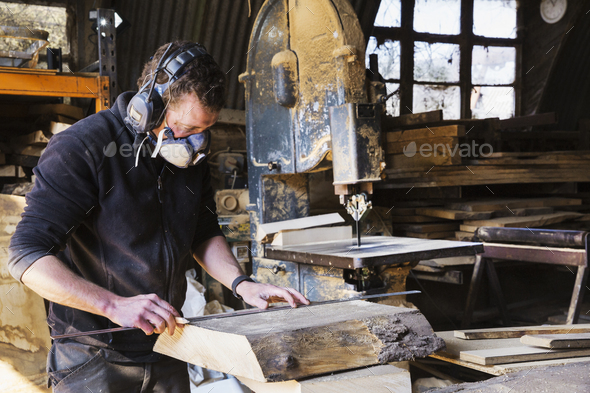 Man working in a carpentry workshop, wearing a respirator and hearing protector, measuring a plank - Stock Photo - Images