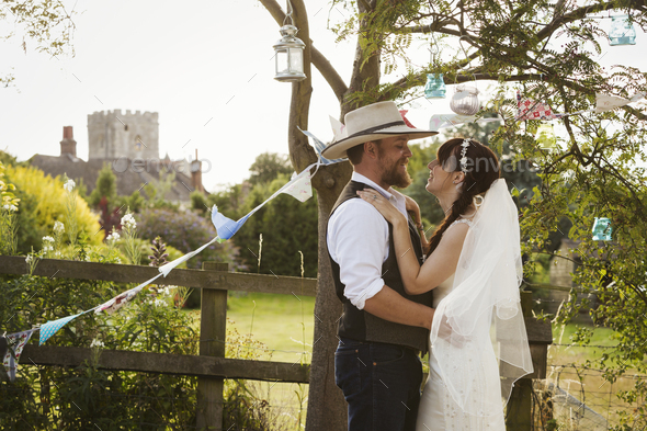 Newlywed couple, a bride and groom standing by a stile, hugging and gazing at each other. - Stock Photo - Images