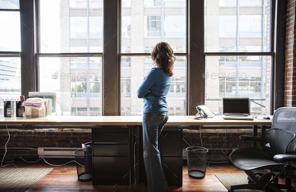 Caucasian woman at office workstation near a large bank of windows. - Stock Photo - Images