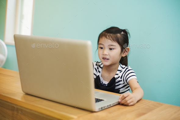 A young girl seated at a laptop computer in a classroom. - Stock Photo - Images
