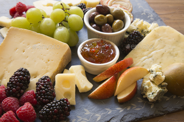 A closeup of a collection of fruits and cheeses. - Stock Photo - Images