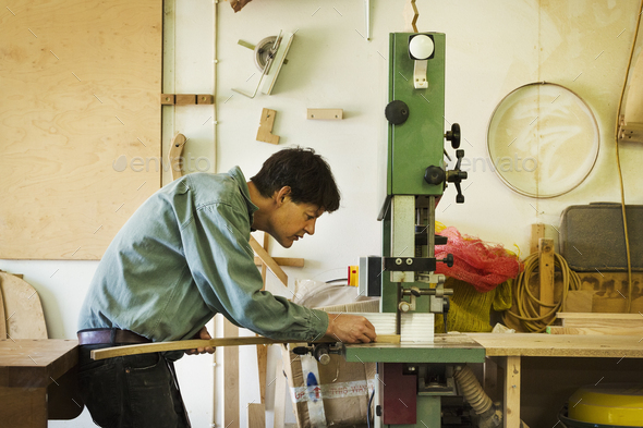 A craftsman holding a piece of wood and using a mortice machine. - Stock Photo - Images