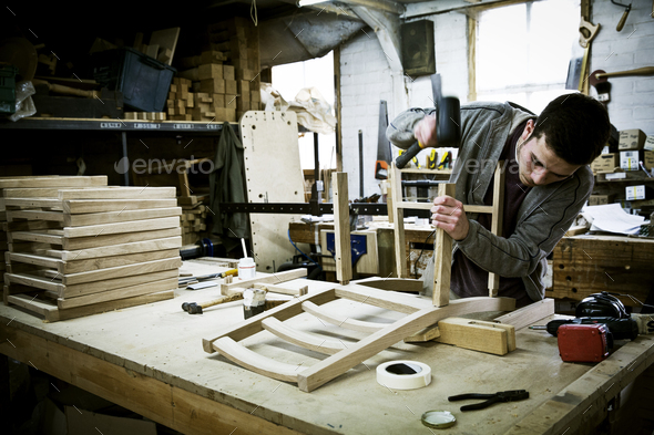 A man working in a furniture maker's workshop assembling a chair. - Stock Photo - Images