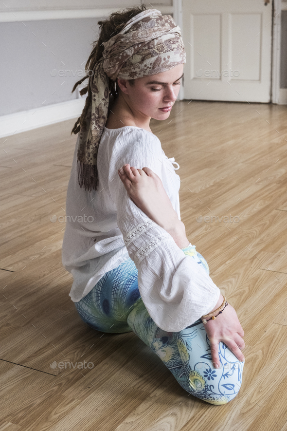 Young woman wearing headscarf and white blouse sitting on floor in yoga pose. - Stock Photo - Images