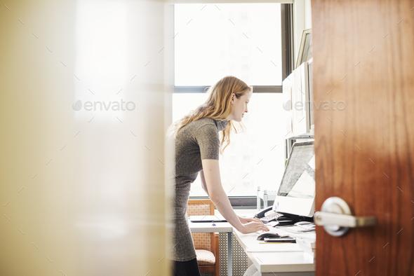 A woman in an office, seen through an open door. - Stock Photo - Images