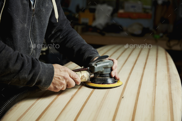A man finishing the surface of a wooden surfboard with an electrical sander. - Stock Photo - Images