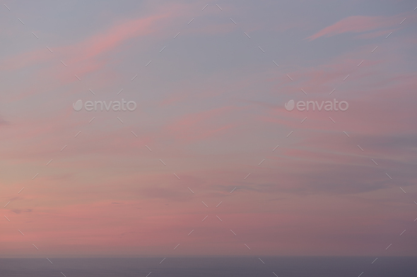 View over the ocean and the sunset sky with pink cloud at dusk. - Stock Photo - Images