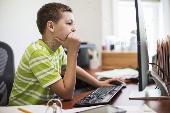 Young caucasian boy at work on a desktop computer system. - Stock Photo - Images
