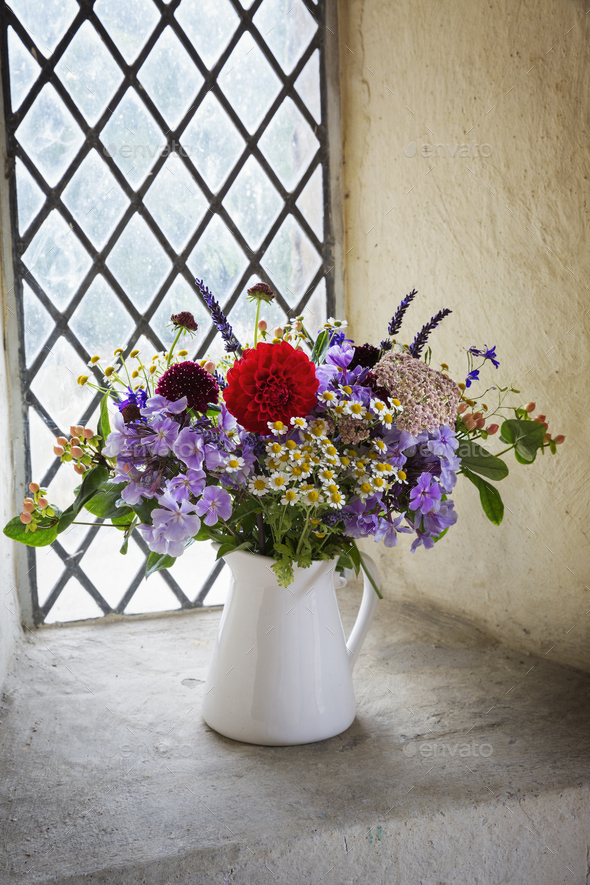 Close up of flower bouquet in a white jug on a windowsill. - Stock Photo - Images