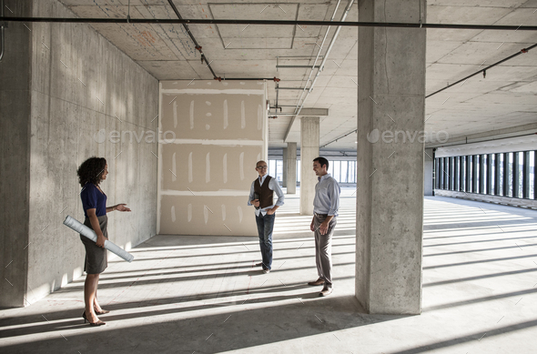 Mixed race team of business people touring a new empty raw office space. - Stock Photo - Images