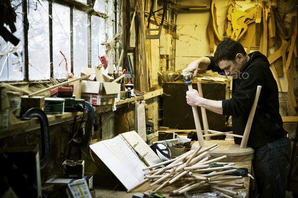 A man working in a furniture maker's workshop. Windsor chairs. - Stock Photo - Images