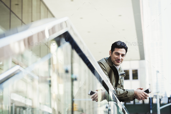 A young man leaning over a balcony rail holding a cellphone and smiling. - Stock Photo - Images