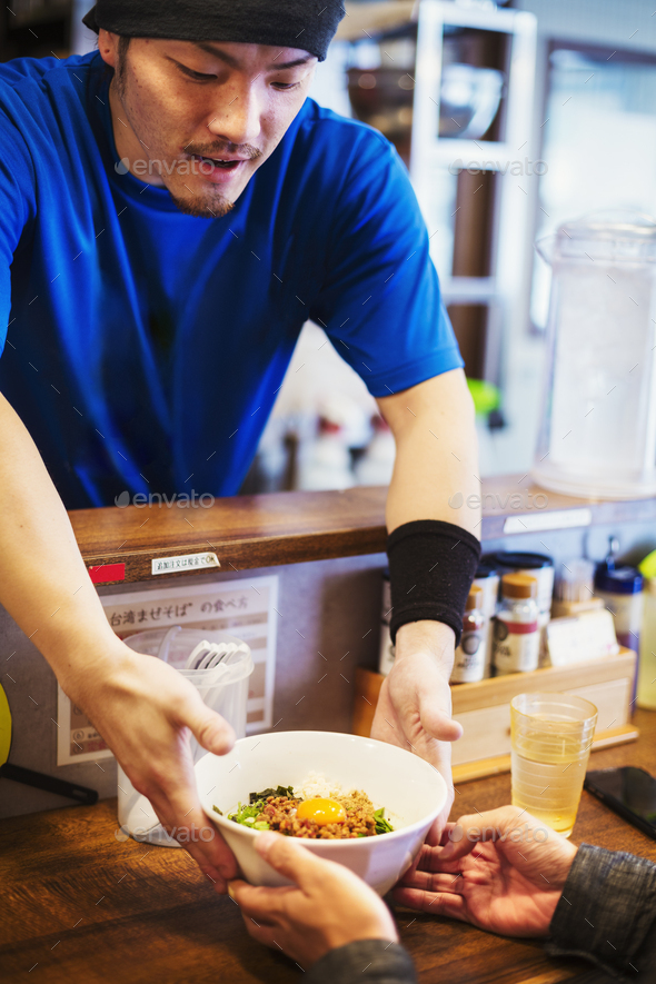 The ramen noodle shop. A chef delivering a bowl of ramen noodles to a customer. - Stock Photo - Images