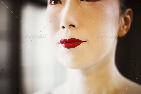 A modern woman creating the traditional geisha vivid red lips by painting on lipstick with a fine - Stock Photo - Images