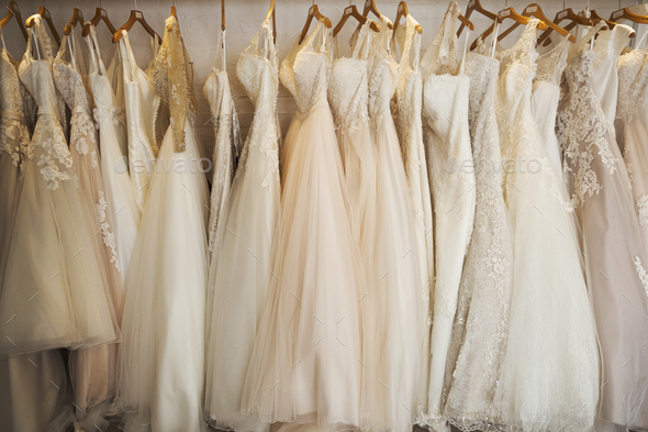 Rows of wedding dresses on display in a specialist wedding dress shop. A variety of colour tones and - Stock Photo - Images