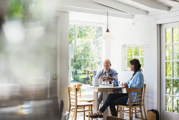 Two people seated at a coffee shop table by a window.  Blurred foreground. - Stock Photo - Images