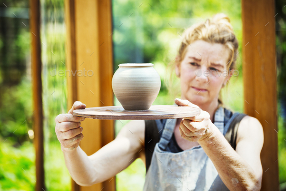 A potter examining a hand thrown pot, wet clay slip, rounded vase with tapering sides. - Stock Photo - Images