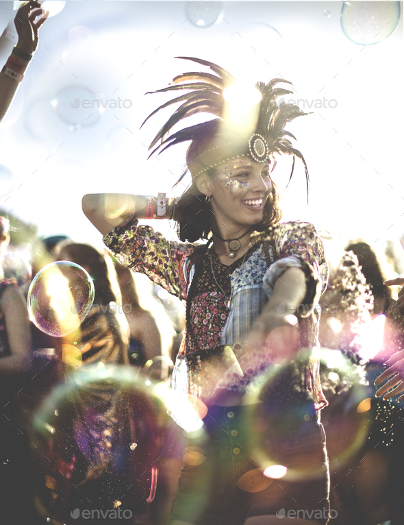 Young woman at a summer music festival wearing feather headdress, dancing among the crowd. - Stock Photo - Images
