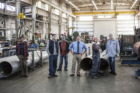 Mixed race team of workers and Hispanic manager in a sheet metal factory. - Stock Photo - Images