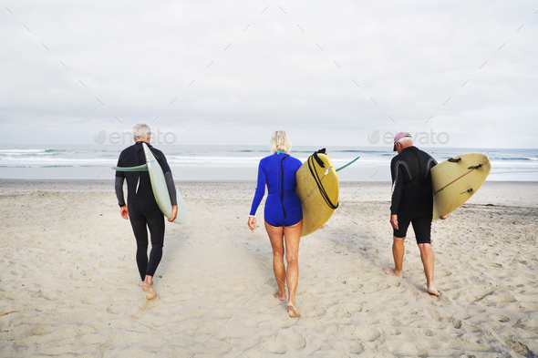 Senior woman and two senior men on a beach, wearing wetsuits and carrying surfboards. - Stock Photo - Images