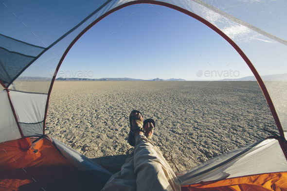Man reclining in camping tent, expansive desert and playa in distance, Black Rock Desert, Nevada - Stock Photo - Images