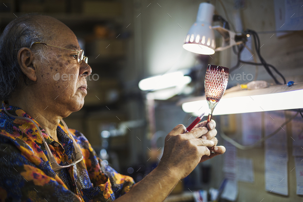 A senior craftsman at work in a glass maker's studio workshop, in inspecting red wine glass with cut - Stock Photo - Images
